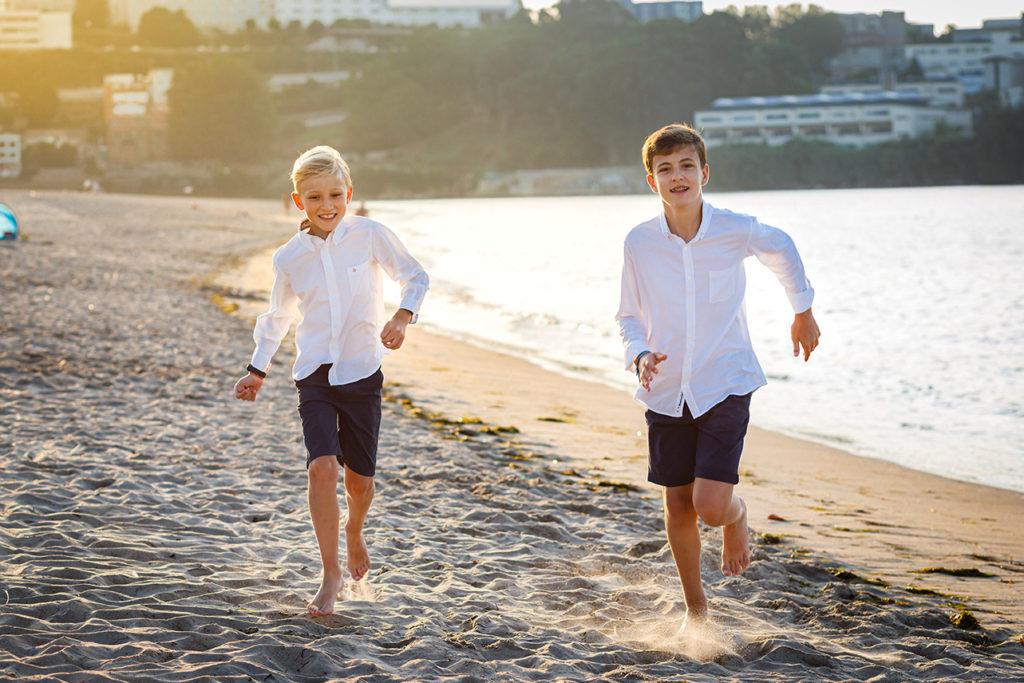 reportajes comunión diferentes divertidos familiares hermanos corriendo por la playa  fotógrafo coruña